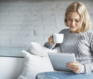 A young woman happily browsing the internet and enjoying a warm beverage
